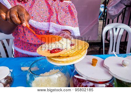 Closeup traditional Colombian streetsnack oblea being prepared adding white sauce top of jam and coc