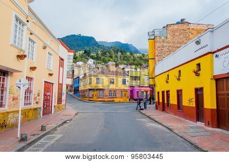 Charming neighbourhood of colorful two storey townhouses with a stone paved street going up and gree