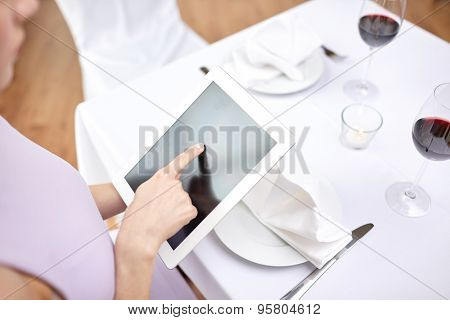 technology, people, food and dinner concept - close up of woman with tablet pc at restaurant