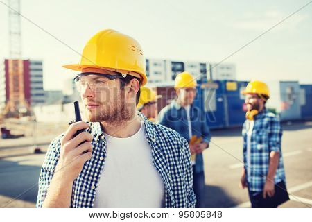 business, building, teamwork, technology and people concept - group of builders in hardhats with radio outdoors
