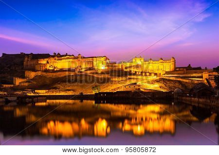 Indian landmark - Amer Fort (Amber Fort) illuminated at night - one of principal attractions in Jaipur, Rajastan, India refelcting in Maota lake in twilight