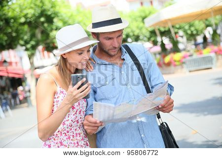 Couple of tourists looking at map in city square