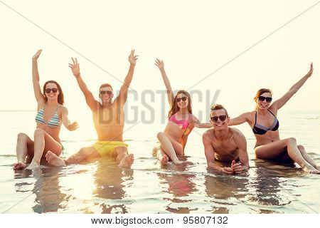 friendship, sea, holidays, gesture and people concept - group of smiling friends wearing swimwear and sunglasses sitting in water on beach