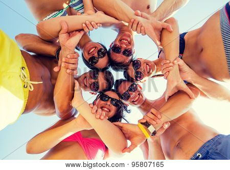 friendship, summer vacation, teamwork and people concept - group of smiling friends wearing swimwear standing in circle over blue sky holding hands connected to each other