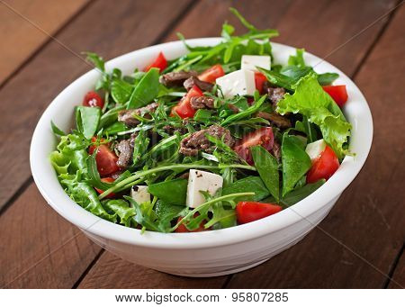 Salad with veal slices, arugula, tomatoes and feta cheese