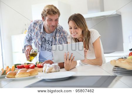 Cheerful couple in kitchen cooking dinner, using tablet