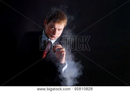 The man in suit smoke a cigar, lots of smoke. A dark background