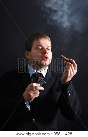 The man smoke a cigar with lots of smoke. A dark background