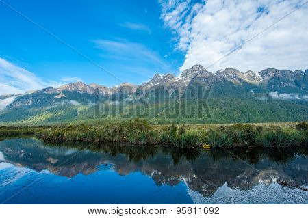 Mirror Lakes are a famous natural landmark on the Milford Road in the Fiordland National Park. Snowy mountains are reflecting in a calm water. New Zealand
