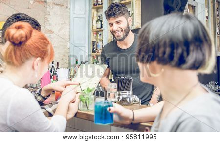 Group Of Friends Choosing Cocktail From The Menu In A Bar