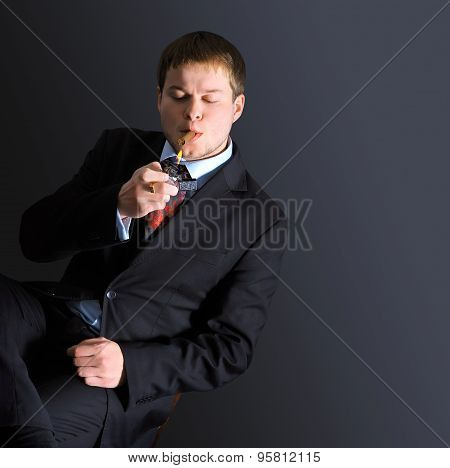 The man smoke a cigar. A dark background