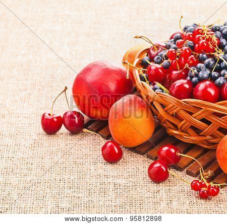 Fresh juicy berries in a basket on burlap background