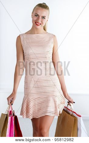 Beautiful Smiling Walking Woman Wearing Dress Holding Colored Paper Bags