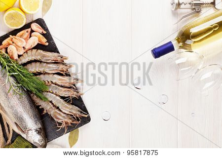 Fresh raw sea food with spices and white wine on wooden table background. Top view with copy space