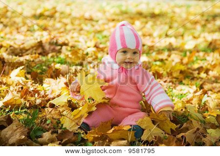 Kid Sits In  Autumn Park