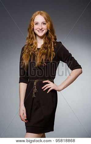 Pretty red hair girl in brown dress against gray
