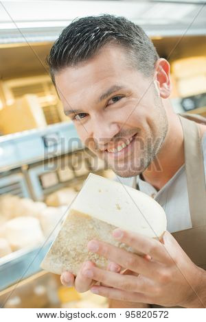 Shop assistant holding chunk of cheese