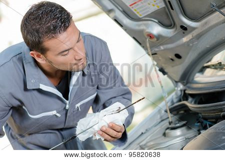 Mechanic checking the oil level of a car