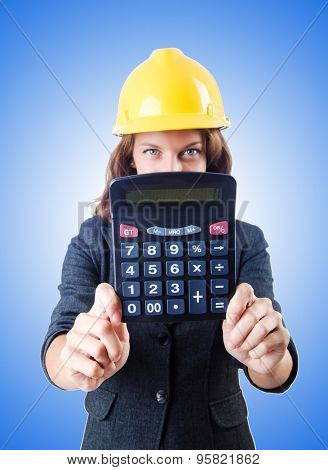 Female builder with calculator against gradient