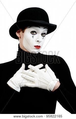 Romantic mime artist puts his hands to his heart performing love. Isolated over white.