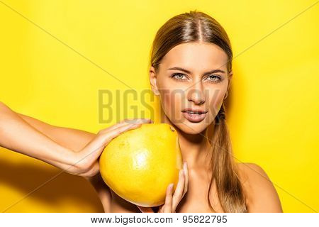Natural young woman holding pomelo over yellow background. Tropical fruits. Summer concept. Healthy eating.
