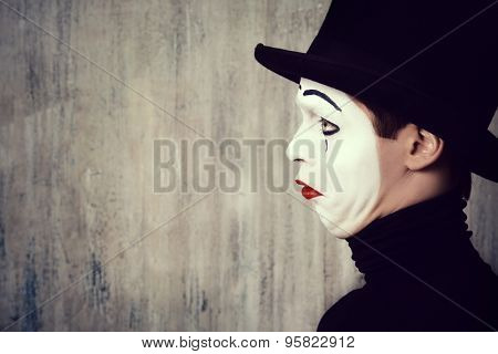 Portrait in profile of a male mime artist performing different emotions. Grunge background.