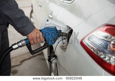 Male hand pumping petrol into car, refueling with nozzle at gas station