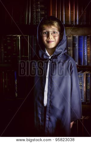 Cute boy in a gown with a hood stands in the library by the bookshelves with many old books. Educational concept. Science. Vintage style.