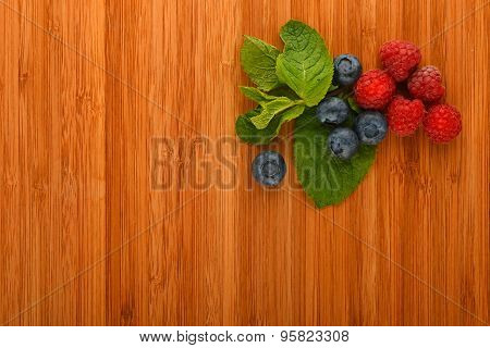 Cutting Board With Blueberries, Raspberries And Mint Leaves