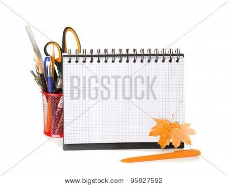 School equipment with pencils,   notebook  and  dry autumn leaves  isolated on white.   Back to school concept.