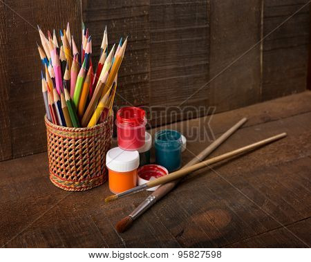 ?olorful  pencils, paints and artist brushes on wood background.