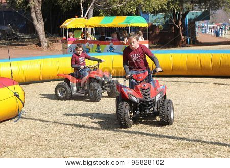 Boys Riding On Quad Bikes At Festival