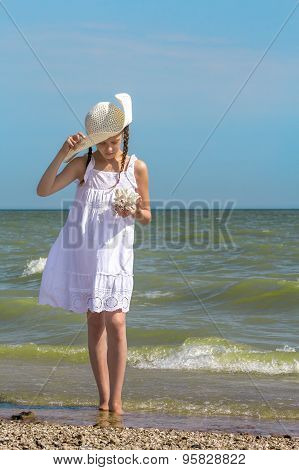 Girl Examines The Coral On The Beach