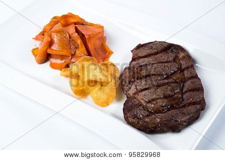 Steak rib-eye garnished with grilled vegetables on white plate. Close up.