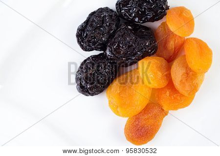 dried apricots and prunes on a white background