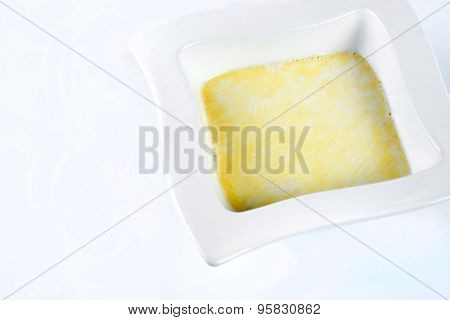 semolina porridge with melted butter on white