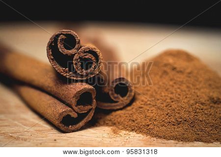 Cinnamon sticks with cinnamon powder on wooden background, Selective focus