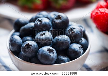 Blueberry in white bowl over linen napkin, close-up