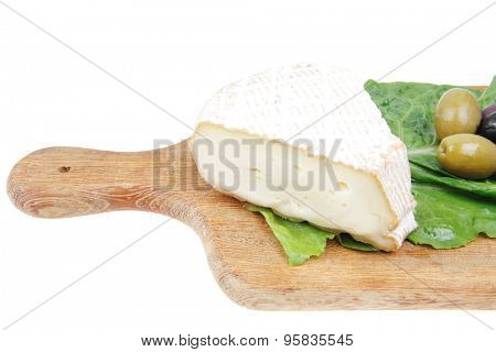 aged camembert cheese on wooden platter with olives and tomato isolated over white background