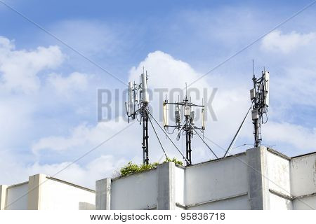 Cell Phone Towers On Resident Building Roof With Blue Sky