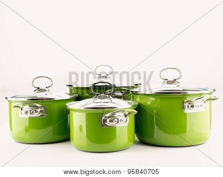 Set of four green enamel pots with lids shot on white