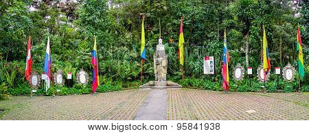 Stone bust sculpture Simon Bolivar surrounded by the flags of several latin american countries from