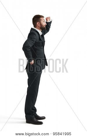 businessman holding his hand near brow and looking forward. isolated on white background