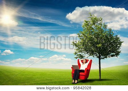 smiley businesswoman with laptop on knees relaxing on the red chair over beautiful landscape with green meadow, tree and blue sky