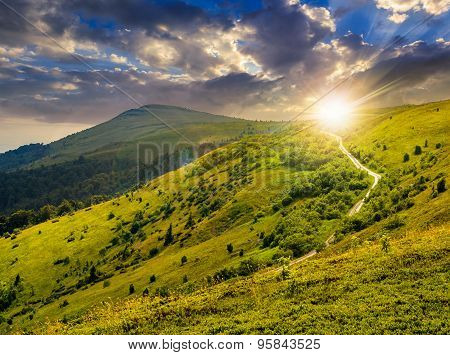 Road Through Hillside In High Mountains At Sunset