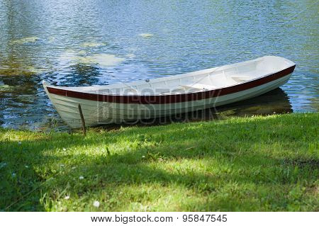 Rowboat At Pond Shore In Summer Park