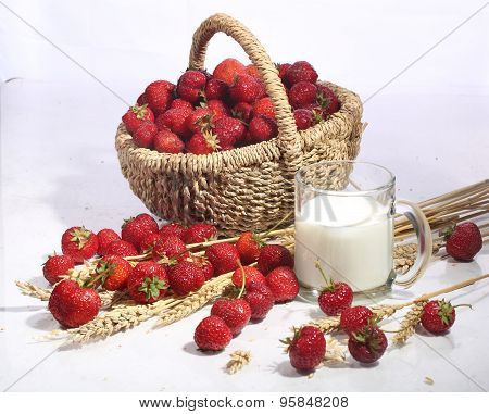 Milk In A Transparent Mug And A Strawberry In A Wattled Basket On A White Background