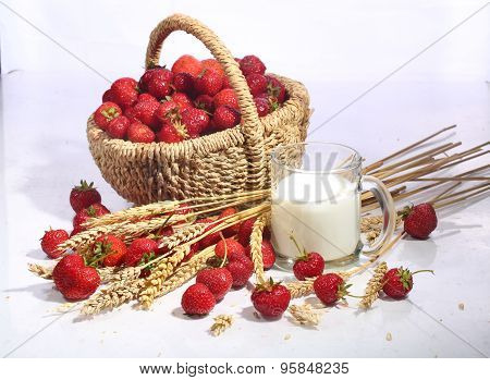Strawberry In A Wattled Basket And Milk In A Transparent Mug On A White Background