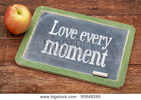 Love every moment advice  - positive words on a slate blackboard against red barn wood