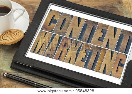 content marketing  - text in grunge letterpress wood type printing blocks on a digital tablet with a cup of coffee